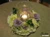 Cocktail tables embellished with delicate wreaths of hydrangeas, roses and lisianthus with hurricane in center